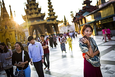 Young woman standing in town square, holding old Polaroid camera, pagoda in the background, Myanmar