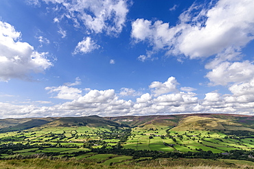 Landscape with fields and distant mountains under a cloudy sky, Peak District National Park, United Kingdom
