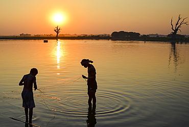 Two boys fishing in a lake at sunset, Amapura, Myanmar, Amapura, Myanmar
