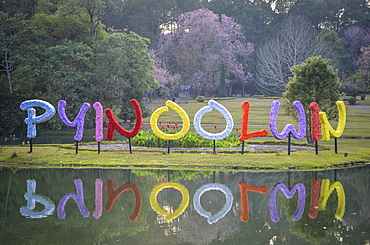 Colourful letters reflected in a lake in a park in Myanmar, Myanmar
