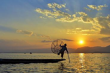Traditional fisherman balancing on one leg on a boat, holding fishing basket, fishing on Lake Inle at sunset, Myanmar