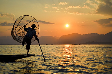 Traditional fisherman balancing on one leg on a boat, holding fishing basket, fishing on Lake Inle at sunset, Myanmar