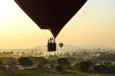 Hot air balloon over landscape with temples at sunset, Bagan, Myanmar