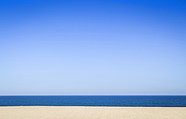 An empty sandy beach and ocean, view out to sea under a clear blue sky, Portugal