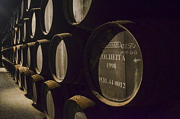 Close up of wooden barrels of Colheita port stacked in a cellar. Port wine production, Porto, Portugal