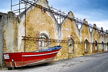 Red boat lying on street lined with dilapidated buildings, Lisbon, Portugal