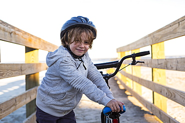 A boy on a bicycle, with helmet on a walkway on the beach, St Simon's Island, Georgia, United States