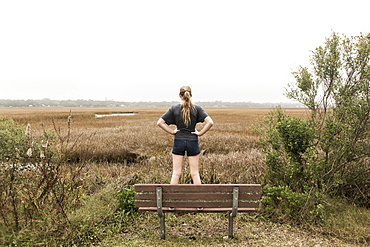 Teenage girl standing on a bench looking out over marshes, St Simon's Island, Georgia, United States