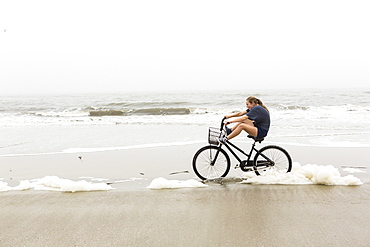 A teenage girl biking on sand on a beach, St Simon's Island, Georgia, United States