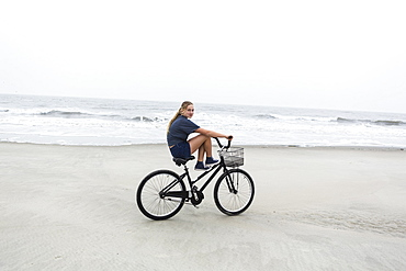 A teenage girl biking on a sandy beach by the ocean, St Simon's Island, Georgia, United States