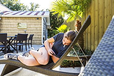 A teenage girl lying in a sunlounger checking her phone, St Simon's Island, Georgia, United States