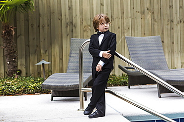 A young boy wearing formal attire standing by pool, St Simon's Island, Georgia, United States