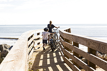 Two children, brother and sister on wooden bridge with bikes, St Simon's Island, Georgia, United States