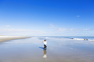 A young boy biking on a sandy beach, St Simon's Island, Georgia, United States