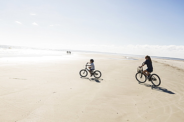 Two children cycling on an open beach, a boy and girl, St Simon's Island, Georgia, United States