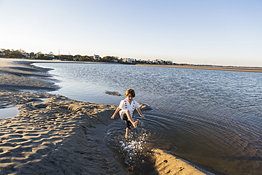 A six year old boy on the beach splashing in shallow water, St Simon's Island, Georgia, United States
