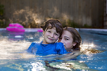 A boy and girl playing in pool in early morning light, St Simon's Island, Georgia, United States