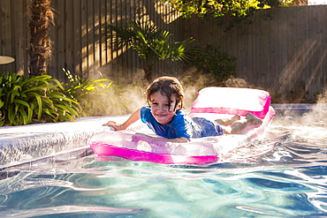 A young boy playing in pool at sunrise, St Simon's Island, Georgia, United States