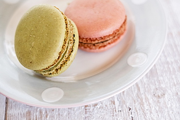 High angle close up of two macaroons on a white plate, United Kingdom