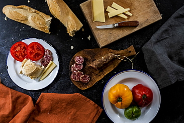 High angle close up of a selection of cheeses, tomatoes, salami and French baguette on white enamel plates on black background, United Kingdom