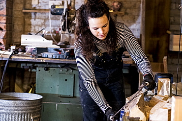 Woman with long brown hair wearing dungarees standing in wood workshop, using plane on piece of wood, Oxfordshire, United Kingdom