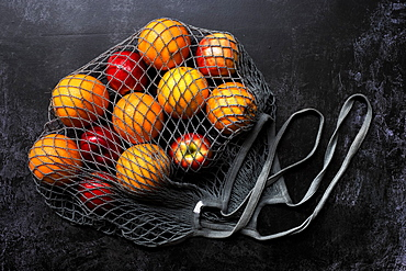 High angle close up of red apples and oranges in grey net bag on black background, United Kingdom