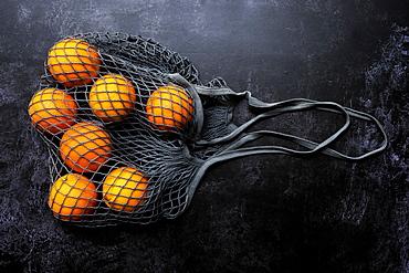 High angle close up of oranges in grey net bag on black background, United Kingdom