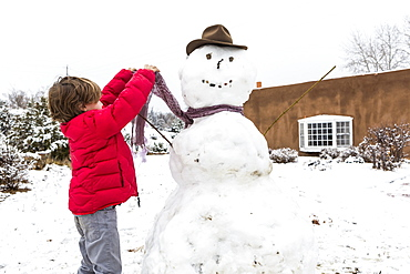 A young boy building a snowman, United States