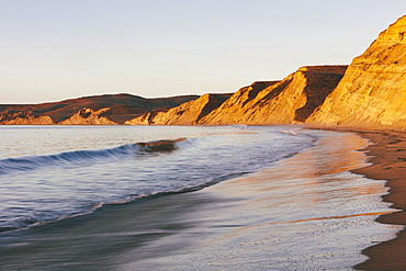 Steep cliffs and beach with surf at dawn, Marin County, California, United States