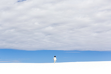 A young boy walking in white sand dunes, a strip of blue sky on the horizon and thick cloud, White Sands National Monument, New Mexico, United States