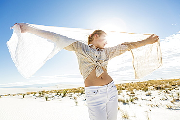A teenage girl dancing with a shawl in the open space of white sand dunes, White Sands National Monument, New Mexico, United States
