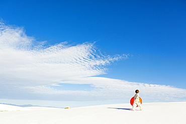 A young boy carrying an orange sled in a white undulating dune landscape, White Sands National Monument, New Mexico, United States