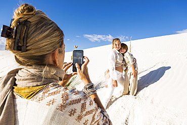 A woman taking picture of her children with a smart phone in white sand dunes landscape under blue sky, White Sands National Monument, New Mexico, United States