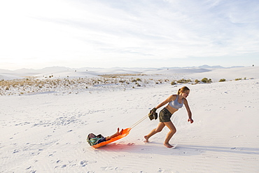 A teenage girl pulling her brother in sled at sunset, White Sands National Monument, New Mexico, United States
