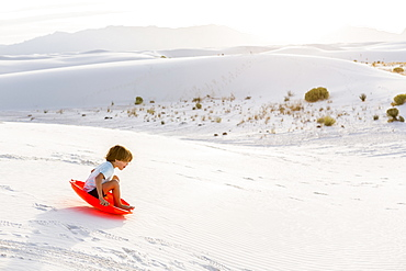 A young boy sledding down white sand dunes, White Sands National Monument, New Mexico, United States