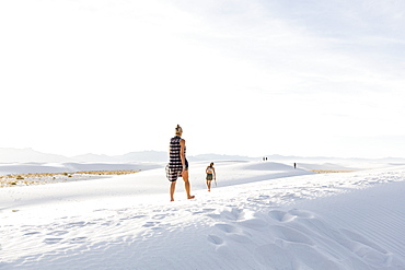 Woman walking in white sand dunes, White Sands National Monument, New Mexico, United States
