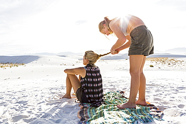 A teenage girl braiding her mothers hair, White Sands National Monument, New Mexico, United States