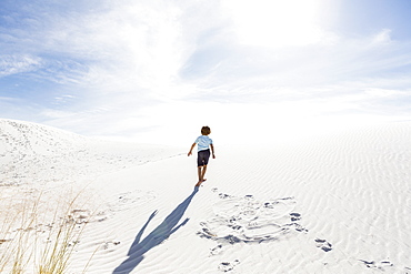 A young boy climbing up white sand dune, White Sands National Monument, New Mexico, United States