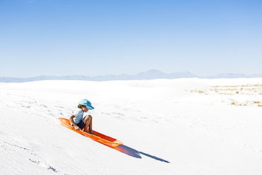 A young boy sledding on sand dune, White Sands National Monument, New Mexico, United States