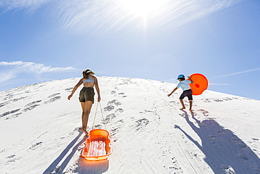 A brother and sister, boy and girl climbing a sand dune, White Sands National Monument, New Mexico, United States