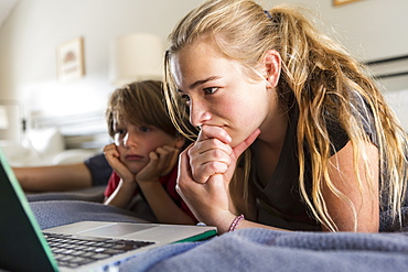 13 year old sister and her brother looking at laptop on bed, United States