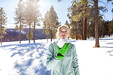 A blonde teenage girl holding a snowball