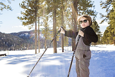 A six year old boy in woodland holding ski poles