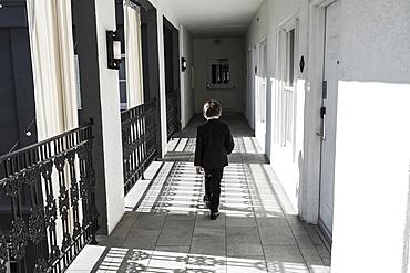 A six year old boy walking down corridor