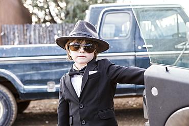 Six year old boy leaning on car open car door
