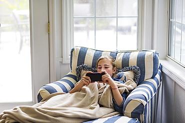 A thirteen year old teenage girl looking at smart phone