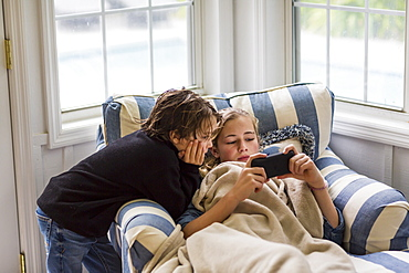 A boy and a teenage girl looking at the screen of a smart phone.