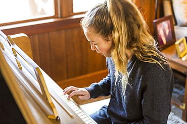Teenage girl playing piano, practising.