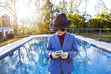 Boy in a suit and dark glasses standing on the edge of water counting dollar bills.