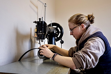 Female saddler sitting in workshop, sewing on saddlery sewing machine, Berkshire, United Kingdom